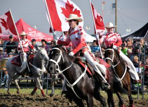 Cowgirls in Canadian themed outfits carry the country's flag while riding their horses.