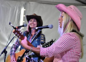 Two women in cowboy hats perform with acoustic guitars.