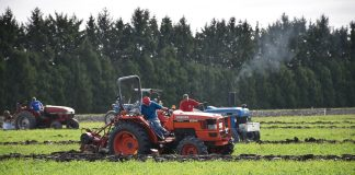 A group of men on tractors plow through a field in competition.