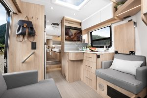 The living room area on the inside of a motorhome features grey seating and light-wood cabinets.