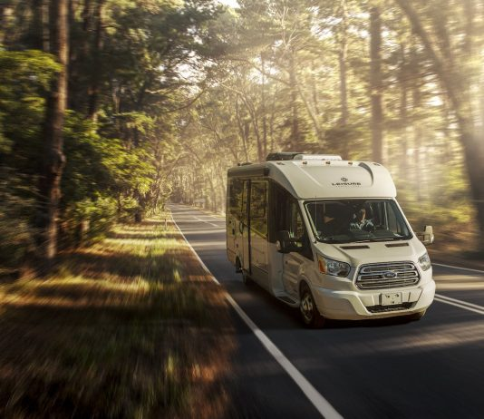 A white motorhome traveling down the road in a forest setting.